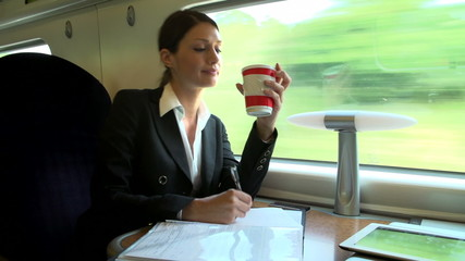 Female Commuter With Coffee On Train Working On Document