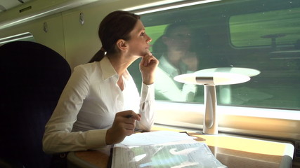 Female Commuter On Train Working On Document