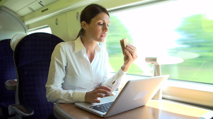 Female Commuter On Train Using Laptop Whilst Eating Sandwich