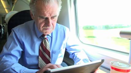 Senior Businessman Commuting On Train Using Digital Tablet