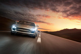 Luxury sports car speeding on empty highway at the sunset