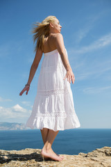 Girl in white sundress on seashore
