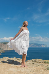 Girl in white sundress on seashore
