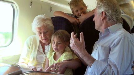 Grandparents And Grandchildren Relaxing On Train Journey