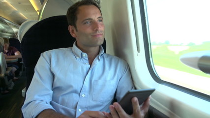 Man Reading E Book On Train Journey