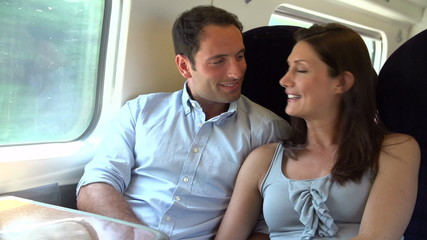 Couple Relaxing On Train Journey Together