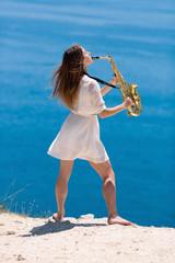 Musician on rocky seashore