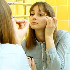 nice girl doing makeup in the bathroom