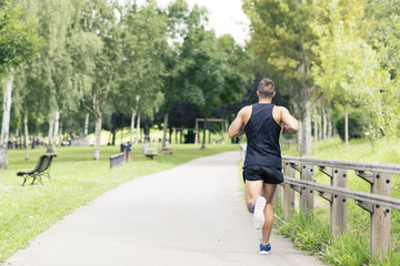 Athletic man running and exercising in the park.
