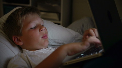 Boy Using Laptop Computer In Bed At Night