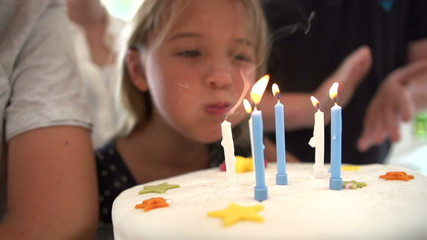 Slow Motion Sequence Of Girl Blowing Out Candles On Cake