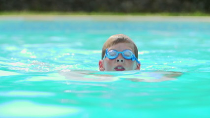 Young Boy Swimming In Outdoor Pool