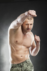 man boxing half naked on grey background