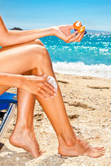 Woman applying sun protection cream at beach.