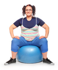 Overweight woman sitting on fitness ball.