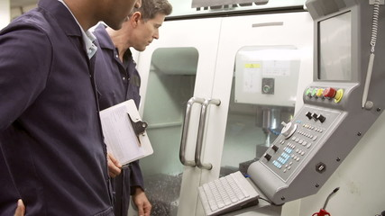 Two Engineers Monitoring Computerized Lathe