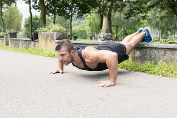 Man training and exercising doing push ups in the park.