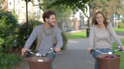 Couple Cycling Through Urban Park Together