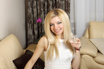 Nice natural blonde girl drinking from a glass