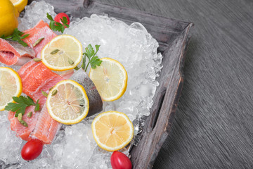 Fresh trout with lemon on a wooden tray