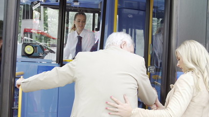 Woman Helping Senior Man To Board Bus
