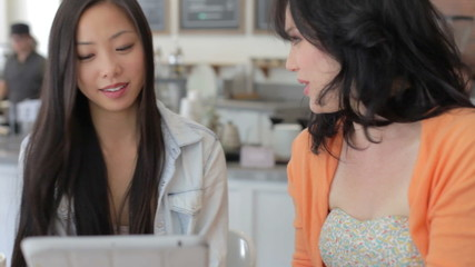 Two Female Friends In Coffee Shop Looking At Digital Tablet