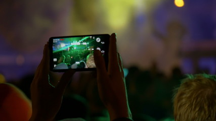 Making video with cell phone at live music concert, festival
