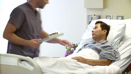 Nurse Talks To Male Patient In Hospital Room