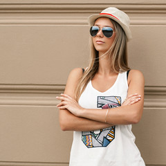 Girl in sunglasses and a hat stands near the wall