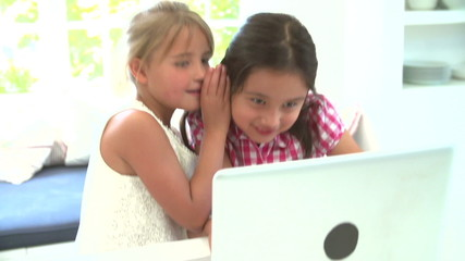 Two Young Girls Using Laptop At Home And Whispering