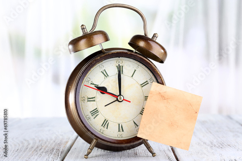 Leinwandbild Motiv Alarm clock with sticker on bright background