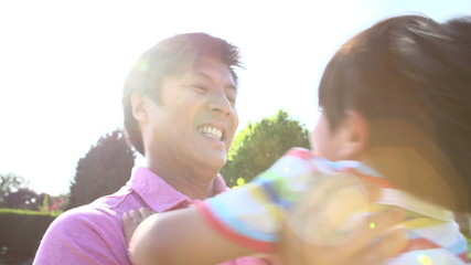 Asian Father Spinning So Around In Summer Garden Together