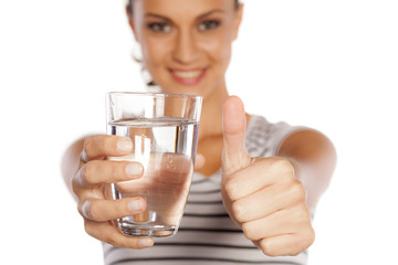 a young woman holding a glass with water and showing thumb up
