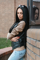Girl in a leather jacket standing near the building