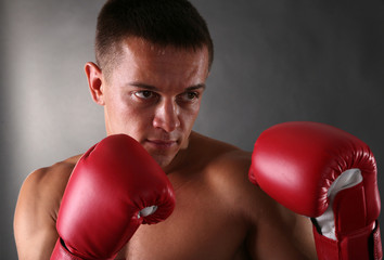 Handsome young muscular sportsman with boxing gloves