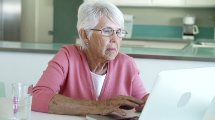 Senior Woman Using Laptop At Home In Kitchen