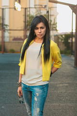 Beautiful girl in a yellow jacket and jeans holds glasses