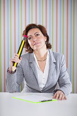 Businesswoman writing with a giant pencil