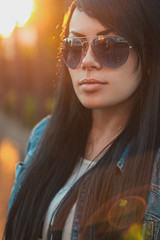 Beautiful girl in sunglasses. sunlight  sunset