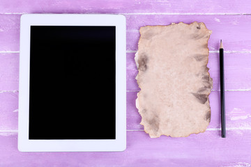 Tablet, piece of paper and pencil on wooden background