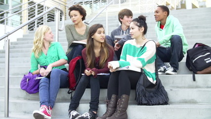Group Of High School Students Sitting Outside Building