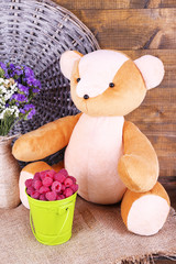 Toy bear, bucket of raspberries and vase of field flowers