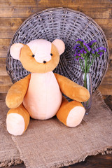 Toy bear and flowers on wicker mat and wooden wall background
