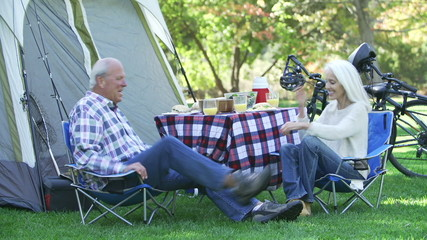 Senior Couple On Camping Holiday Setting Off On Cycle Ride