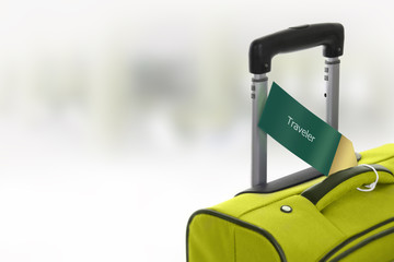 Traveler. Green suitcase with label at airport.