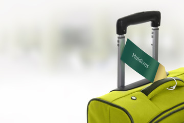 Maldives. Green suitcase with label at airport.