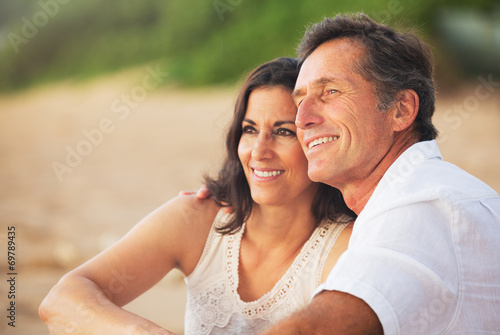Leinwandbild Motiv Mature Couple Enjoying Sunset on the Beach