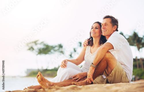 Mature Couple Enjoying Sunset on the Beach - 69789448