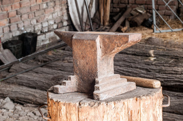 Rustic anvil on wooden stump.