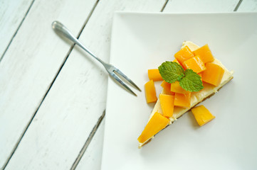 Mango cheesecake on white plate with fork